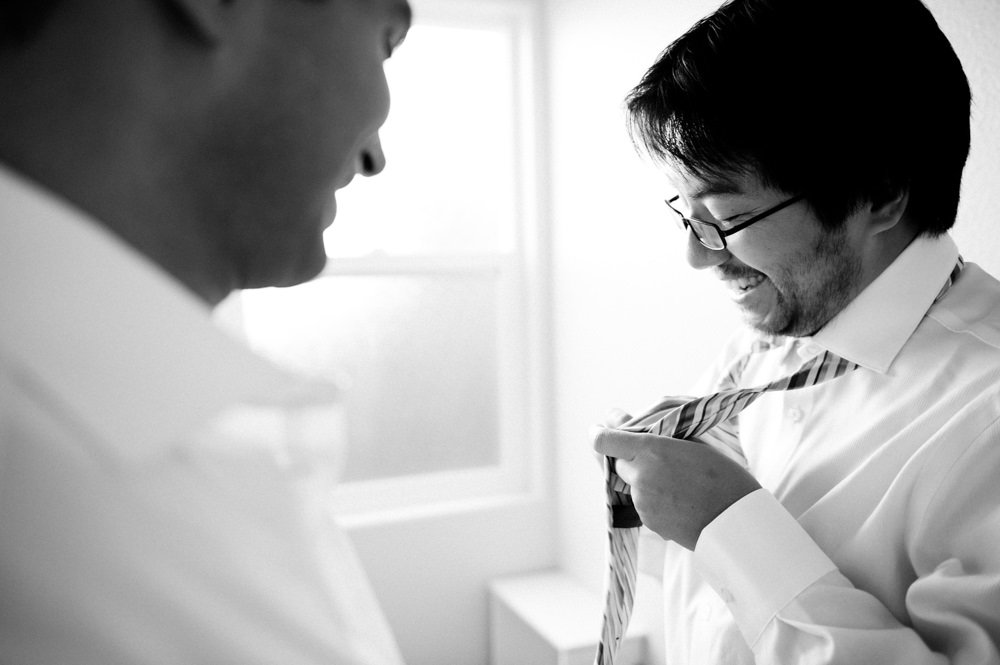 Groom Putting On Tie Wedding Portrait