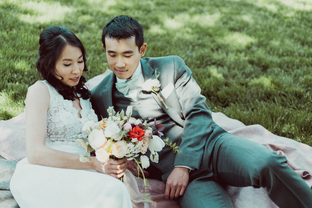 Bride and groom laying on grass at Piedmont Community Hall wedding