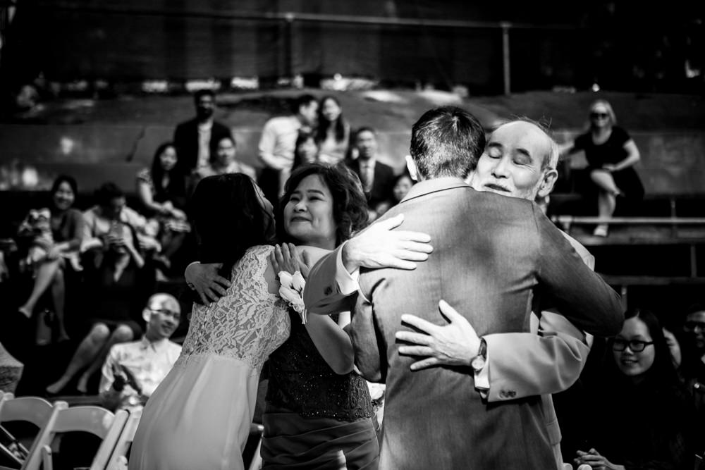 Black and white candid shot of groom hugging father at Piedmont Community Hall wedding