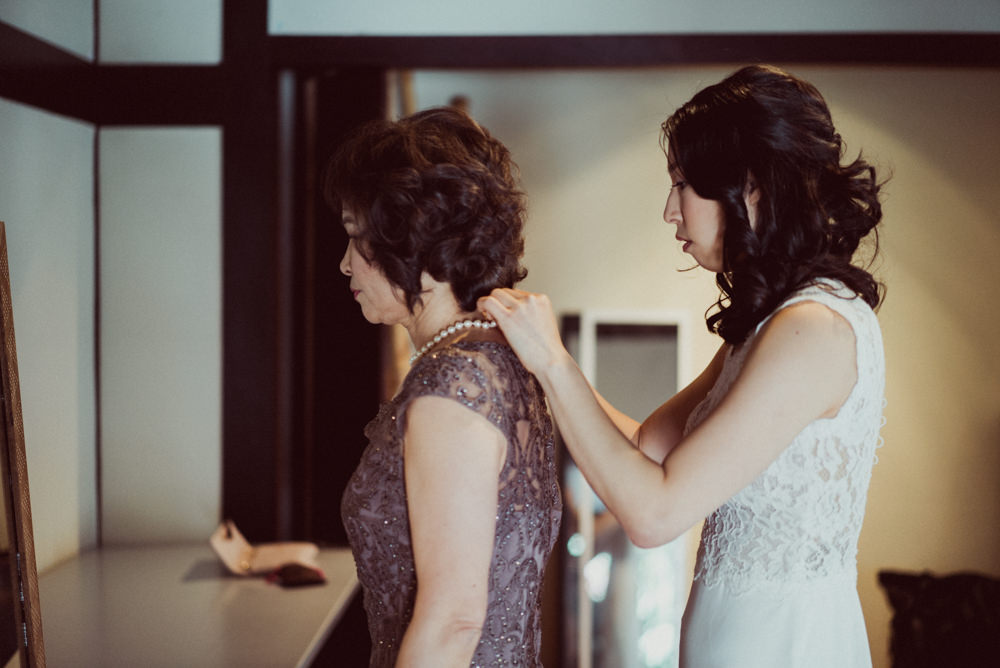 Bride helping mother with necklace at Piedmont Community Hall wedding