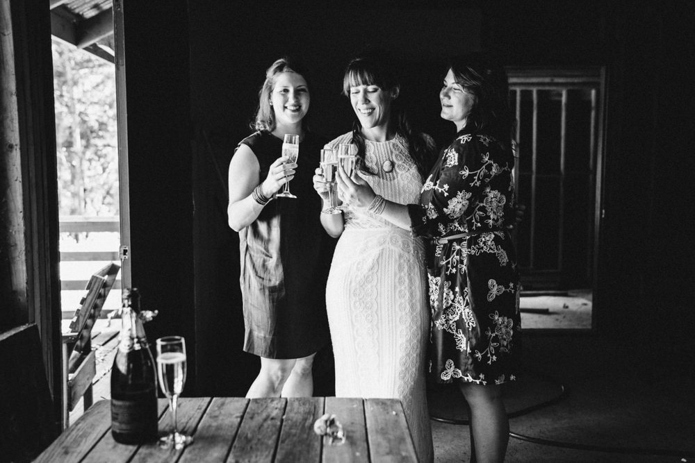 Black and white bridesmaid drinking wine in cabin