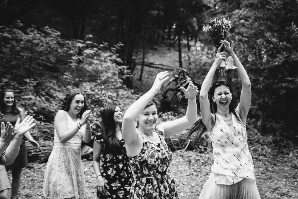 Woman catches bouquet during outdoor wedding