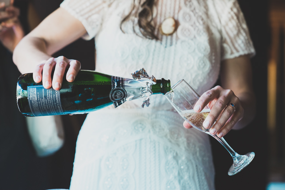 Bride pouring champagne during cabin inspired summer wedding