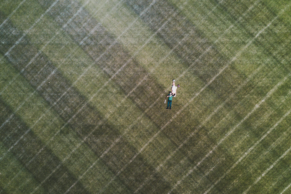 Drone shot of couple on Oakland Coliseum Ricky Henderson field