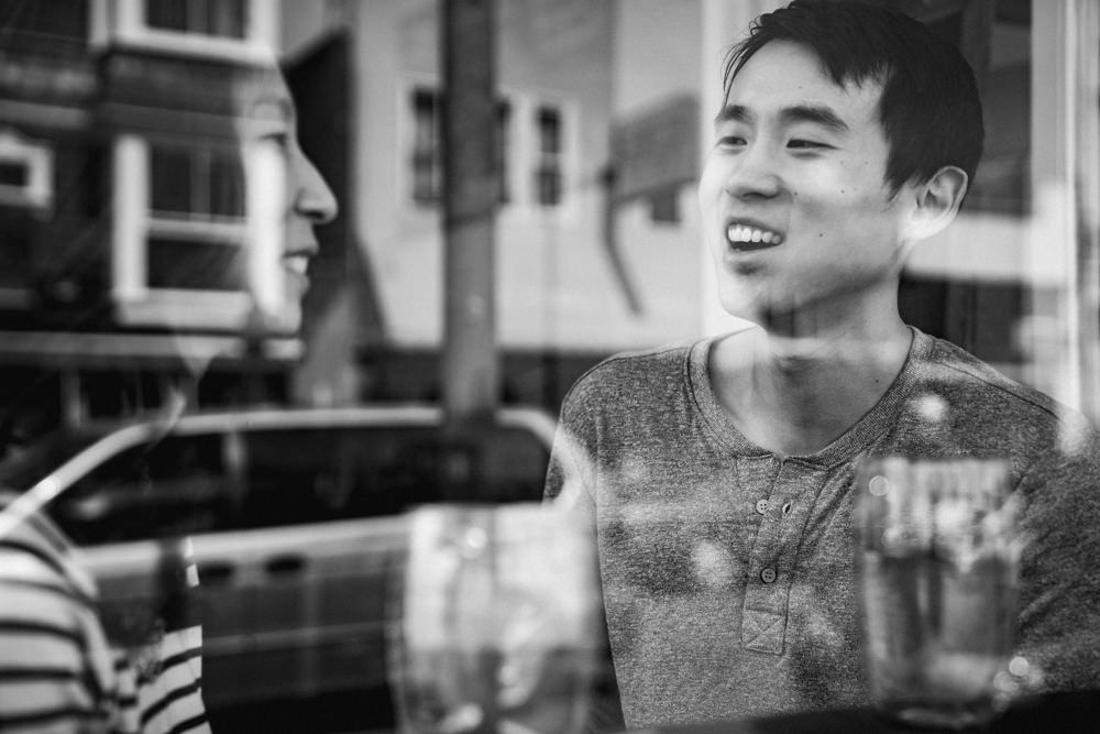 Couple through window reflection at coffee shop during engagement shoot