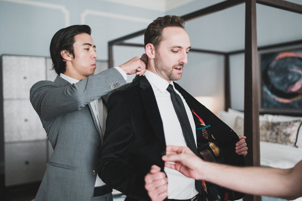 Candid wedding photo of groom showing off velvet suit jacket