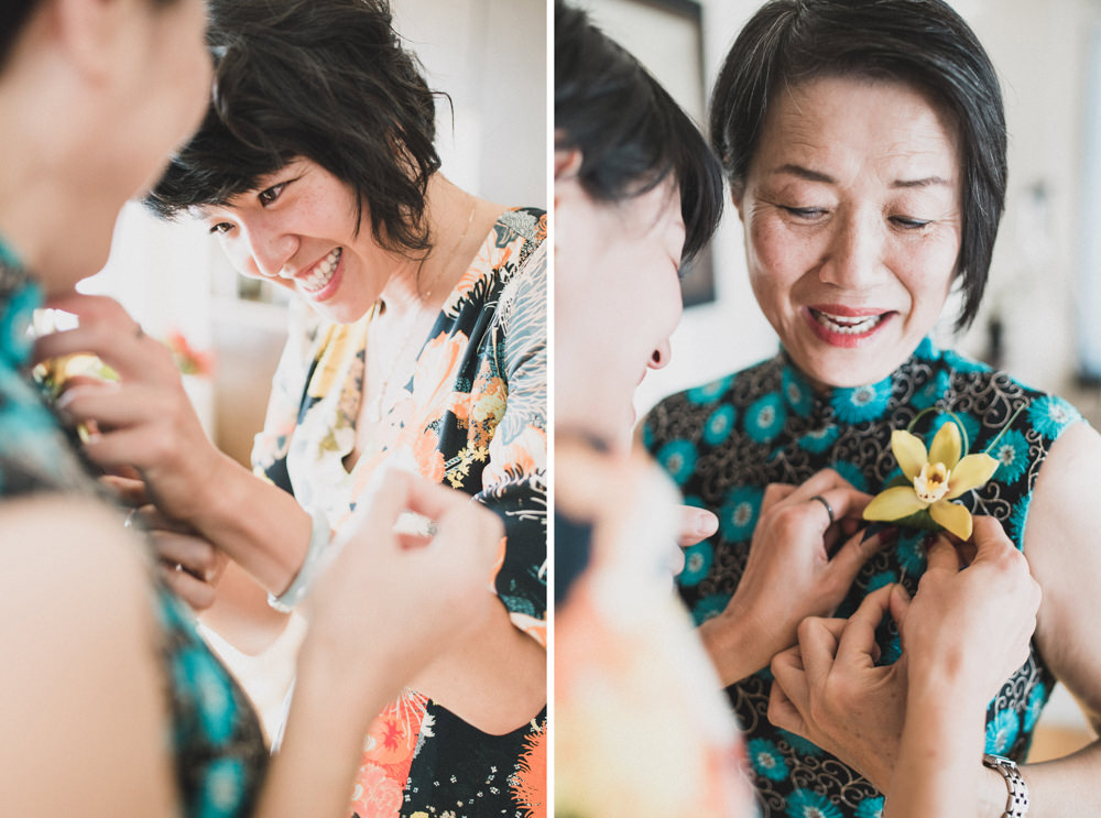 Bride in floral dress putting boutonniere on mother before wedding