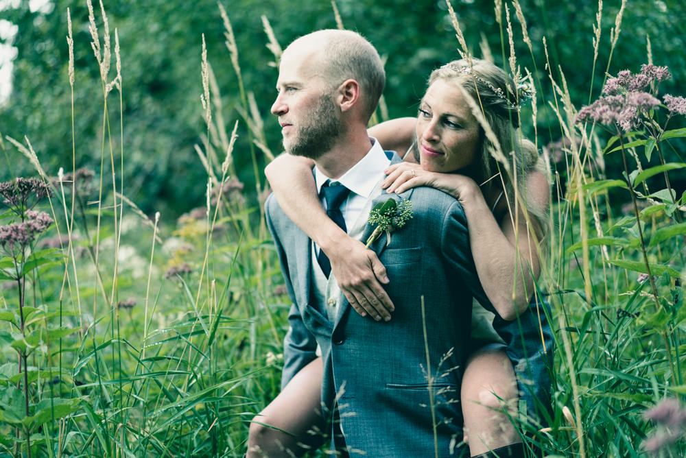 Bride and groom piggy-back wedding shoot in wildflowers field