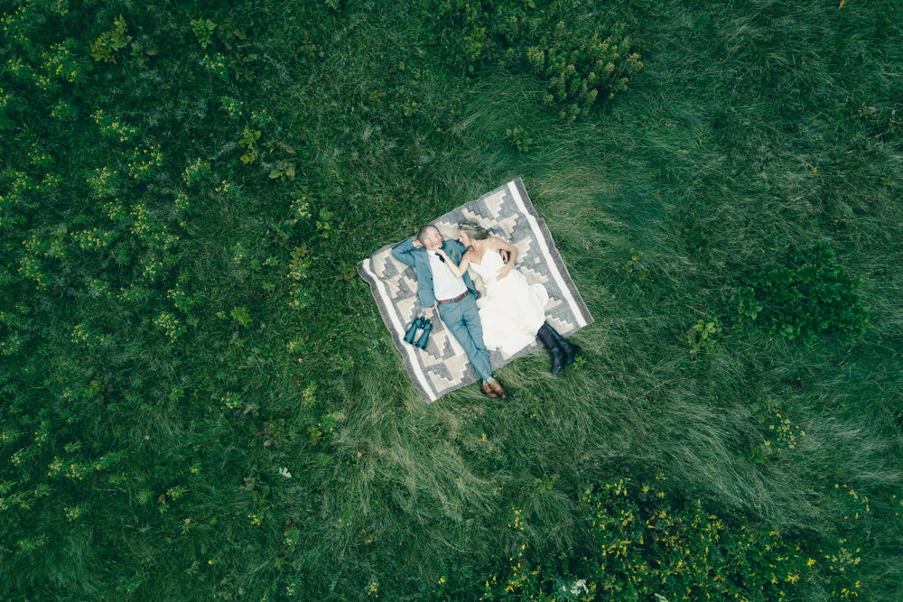Wedding drone shot idea of bride and groom on picnic blanket