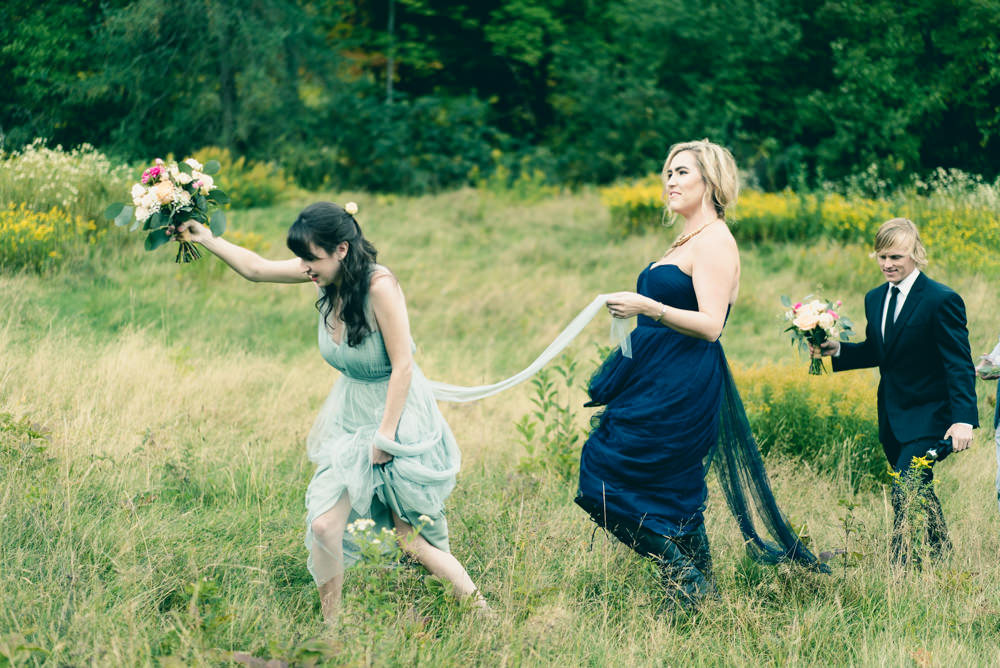 Funny shot of bridesmaid helping each other through field