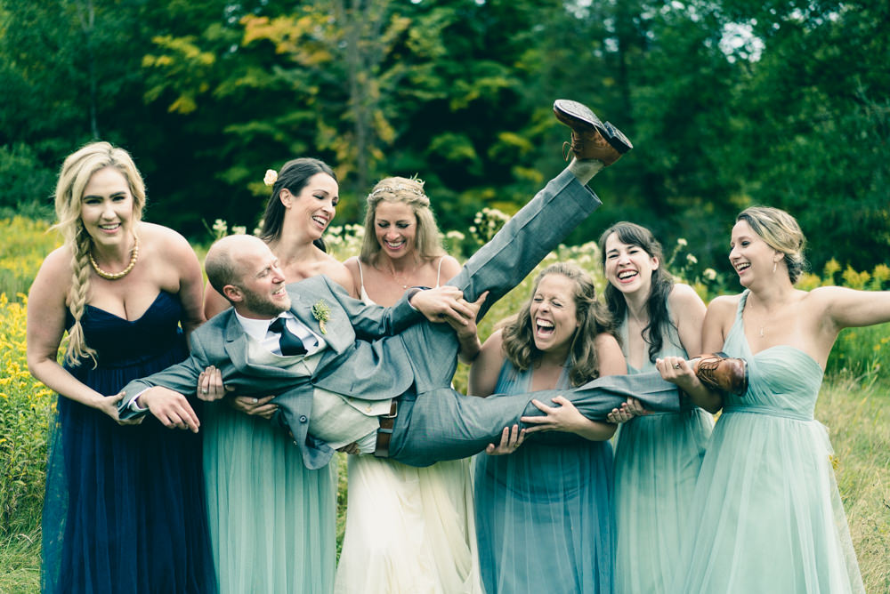 Funny and creative wedding party bridal shoot idea of carrying groom