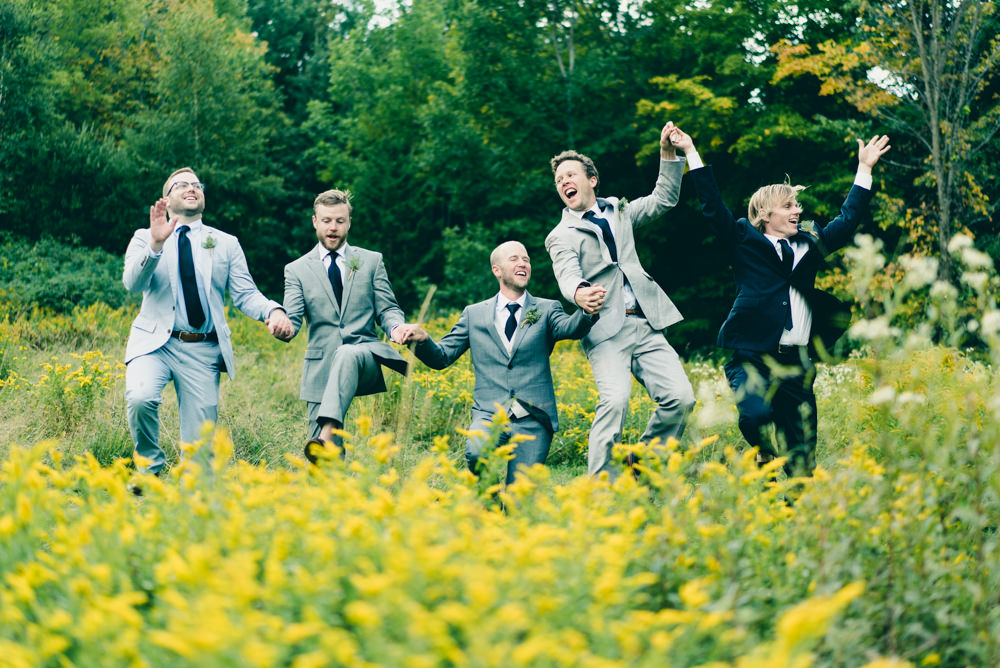 Funny and creative shot of groomsmen holding hands and jumping through field of flowers