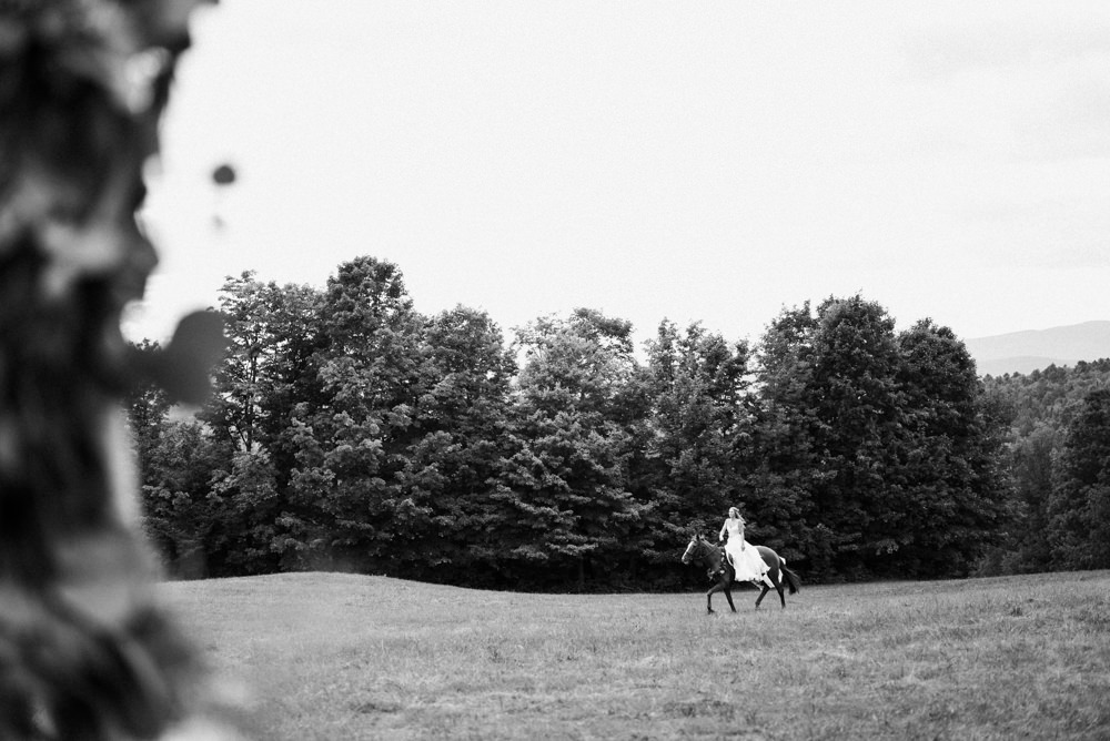 Black and white shot of bride riding horse to wedding ceremony in Vermont