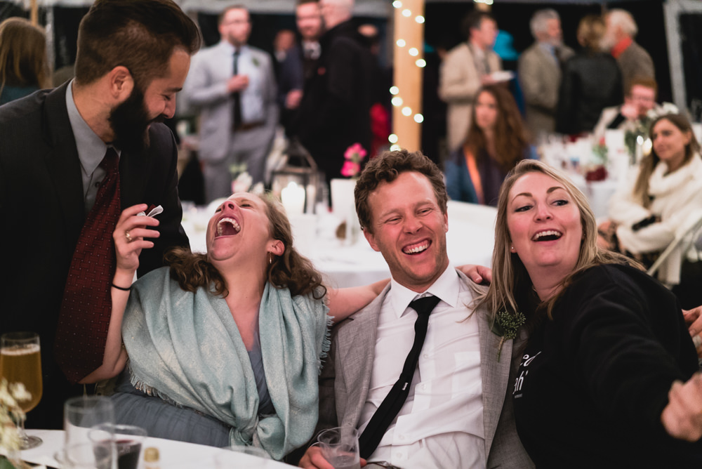 Candid shot of people laughing at outdoor wedding