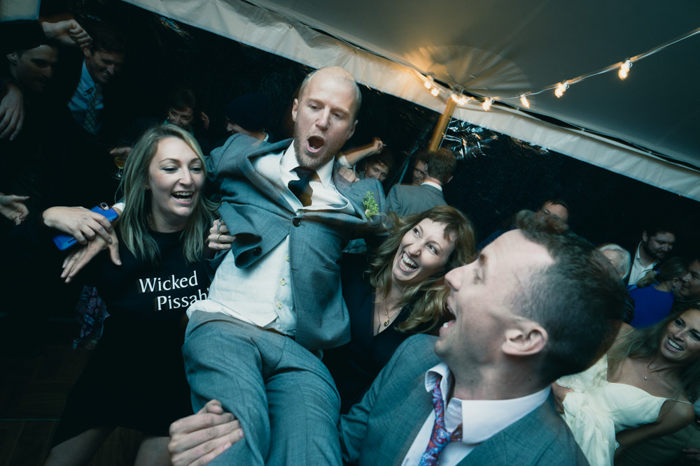 Crazy wedding shot of groom being carried by Wicked Pissah girl