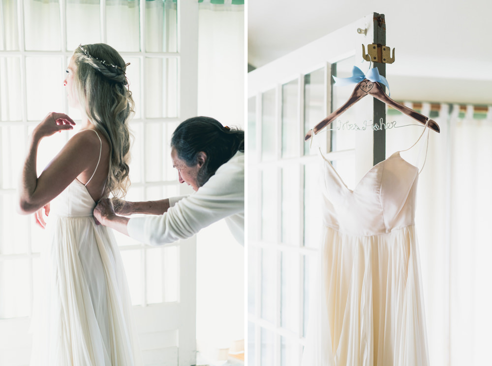 mother helping bride put on cream chiffron wedding dress in Vermont